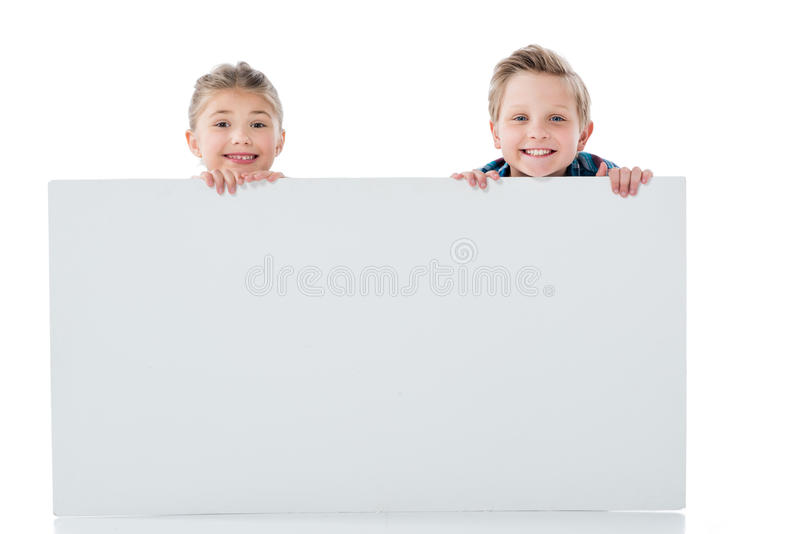Adorable siblings holding blank white banner and smiling at camera stock photography