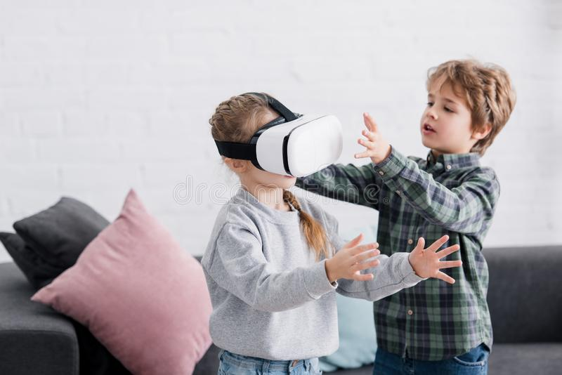 adorable siblings playing with virtual reality headset stock image