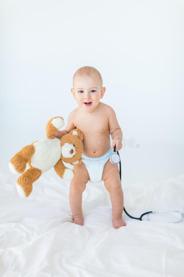 Adorable small baby boy standing on bed and holding stethoscope with teddy bear stock photo