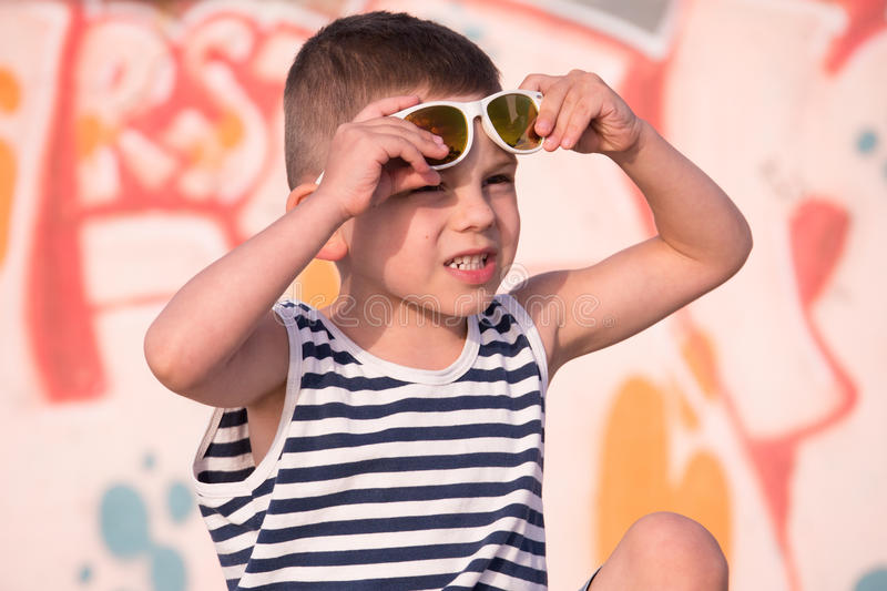 Adorable small boy in sunglasses and sailor shirt on graffiti wall background. Adorable little boy in sunglasses and sailor stripes shirt on yellow and pink stock photos