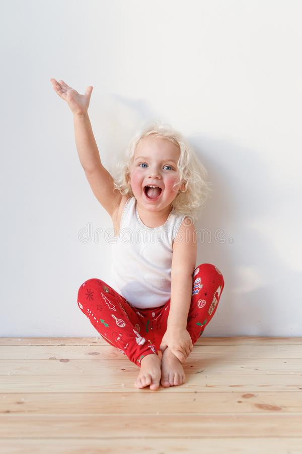 Adorable small female child wears pyjamas, sits on wooden floor raises hands as happy to see affectionate parents stock photo