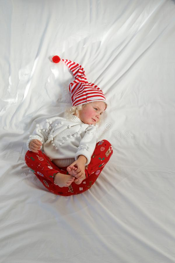 Adorable small kid wears Christmas hat, white sweater and red trousers, looks aside with dreamful expression, lies on stock photo