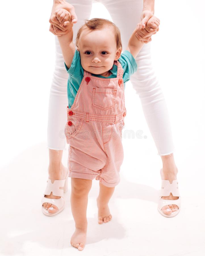 Adorable small toddler. Cute little baby learn to walk. Small child walking with help, motor skills. Little boy child. Develop gross motor activity. Toddler royalty free stock image