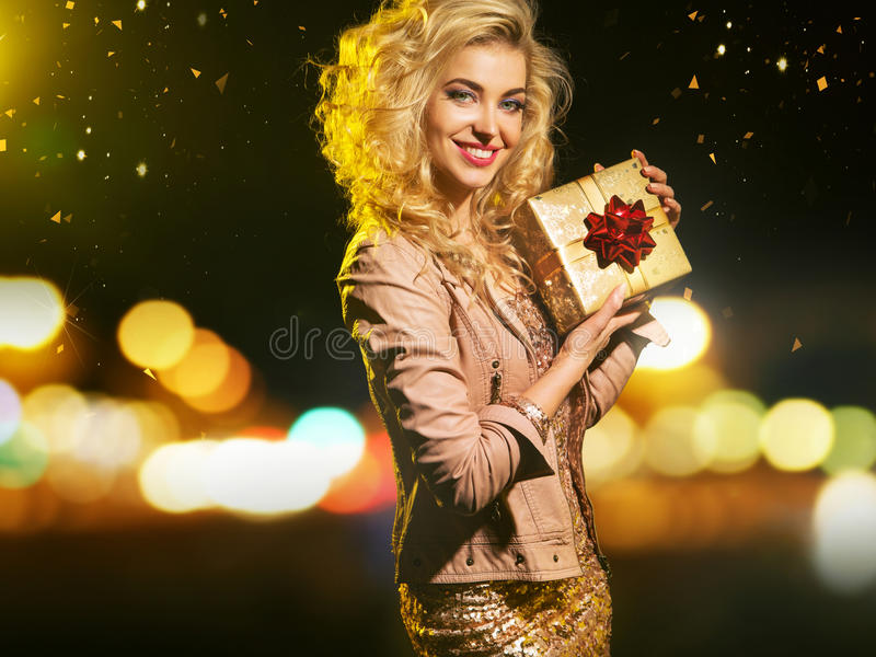 Adorable smart woman holding the gift royalty free stock image