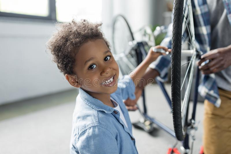 Adorable smiling african-american boy repairing bicycle stock photo