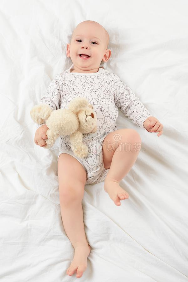 Adorable smiling baby boy with blue eyes lying on a bed with his favourite stuffed teddy bear toy, looking at camera. Cute toddler in pyjamas full body stock images