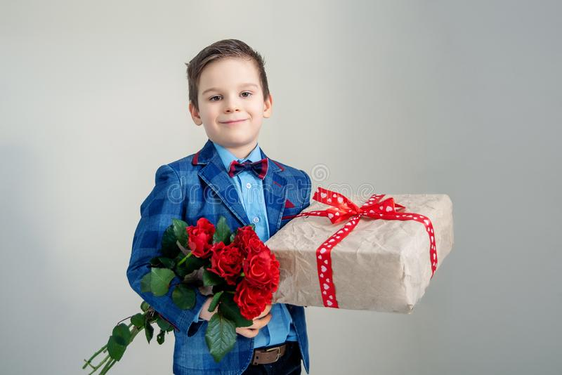 Smiling boy with bouquet of flowers and a gift on a light background stock image