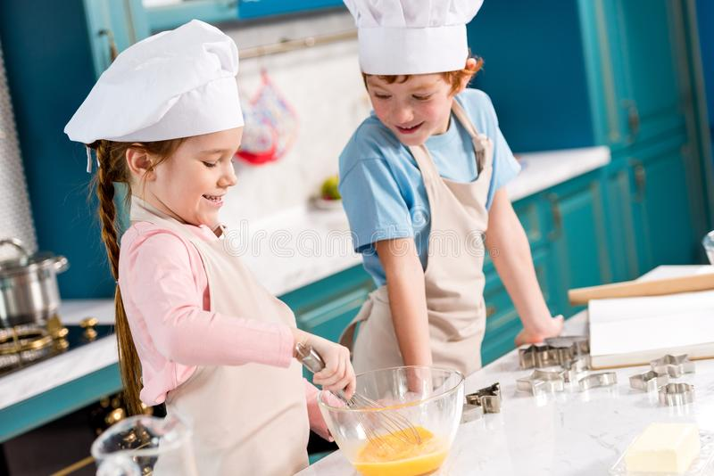 Adorable smiling children in chef hats and aprons making dough together. In kitchen stock photos