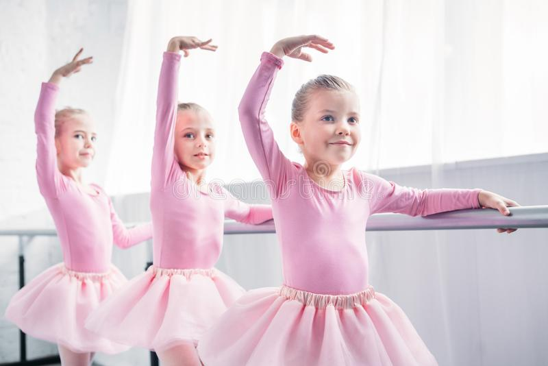 adorable smiling children in pink tutu skirts dancing in ballet royalty free stock images