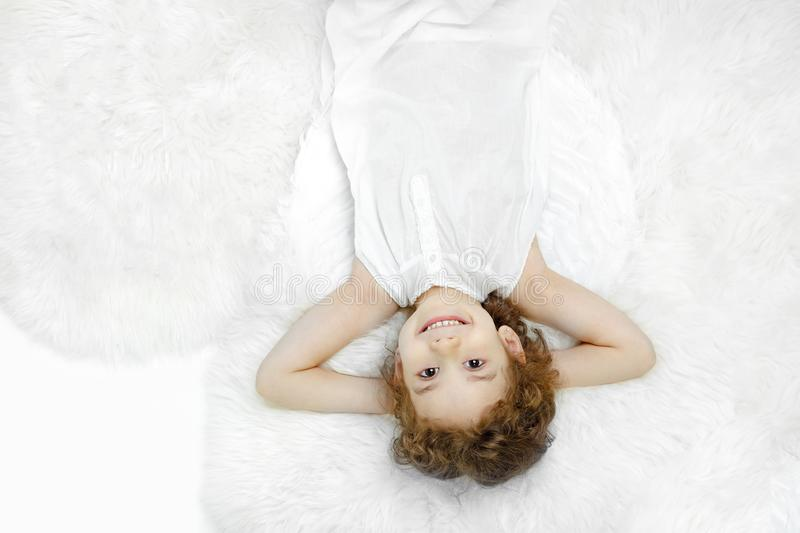 Beautiful curly little girl lying down on fur and looking at camera, in white dress and wings, over white background. royalty free stock image