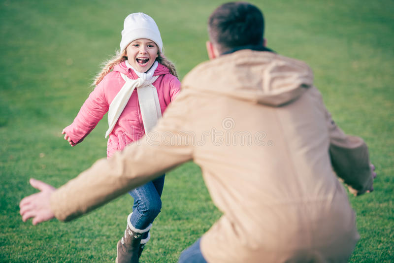Adorable smiling girl running to father. Adorable smiling little girl running to father standing with open arms on green grass stock photos