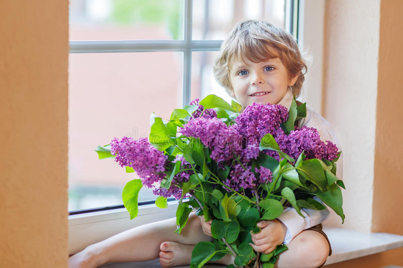 Adorable smiling little boy with blooming purple lilac flowers stock image