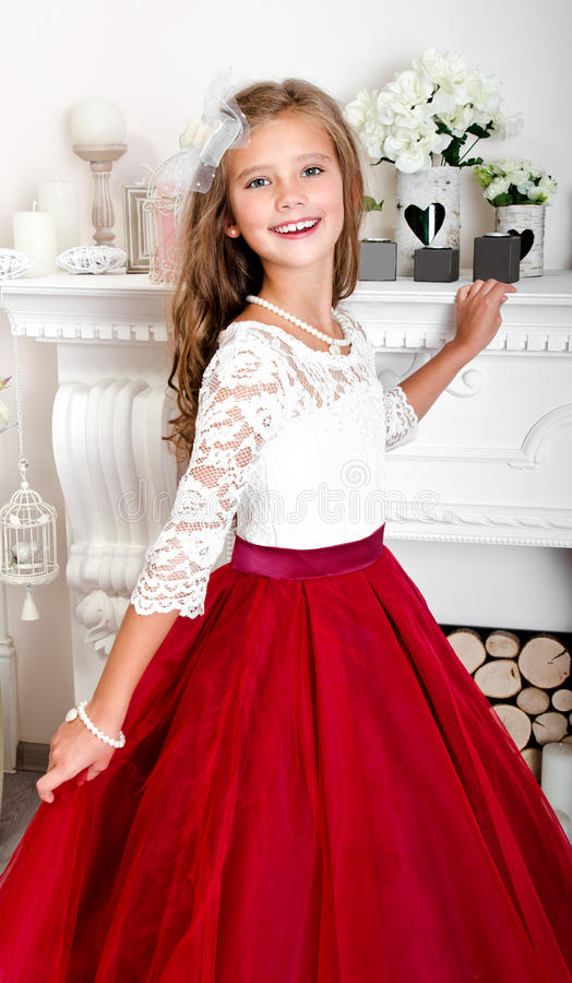 Adorable smiling little girl child in princess dress. Near the fireplace royalty free stock image