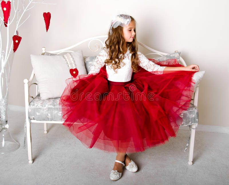 Adorable smiling little girl child in princess dress. Sitting on the sofa royalty free stock photography