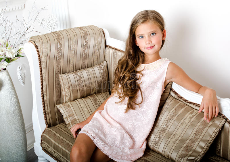 Adorable smiling little girl child in princess dress. Sitting on the sofa stock image