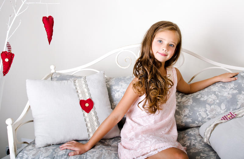 Adorable smiling little girl child in princess dress. Sitting on the sofa royalty free stock images