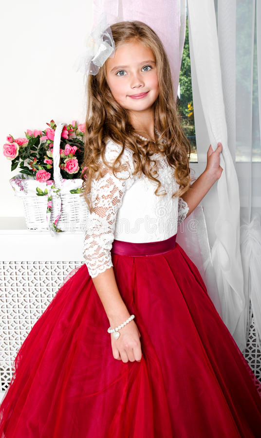 Adorable smiling little girl child in princess dress. Standing near the window stock photography