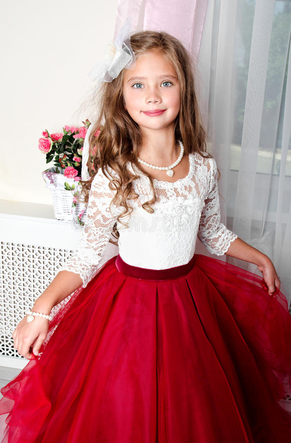 Adorable smiling little girl child in princess dress. Standing near the window royalty free stock image