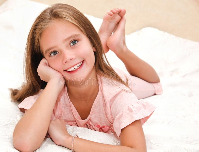 Adorable smiling little girl child is resting on a bed. At home royalty free stock photos