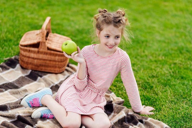 adorable smiling little girl holding green apple while sitting on plaid royalty free stock images