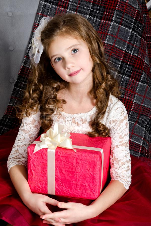 Adorable smiling little girl in princess dress holding gift box. In christmas time birthday royalty free stock images
