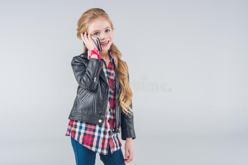 Adorable smiling little girl talking on smartphone royalty free stock photos