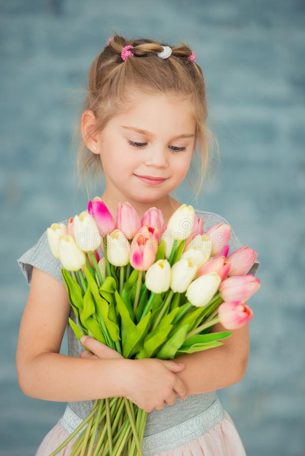 Adorable smiling little girl with tulips by the window stock photo