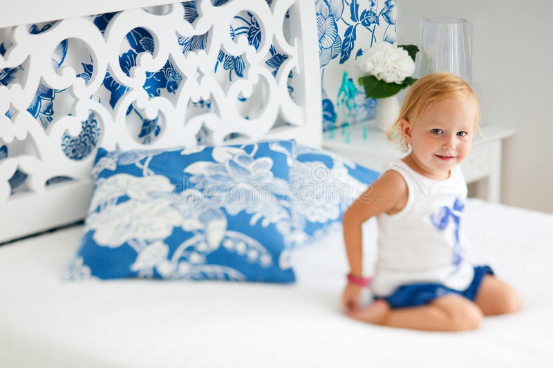 Adorable smiling toddler girl in bedroom. Portrait of adorable smiling toddler girl sitting on bed in nicely decorated bedroom royalty free stock images