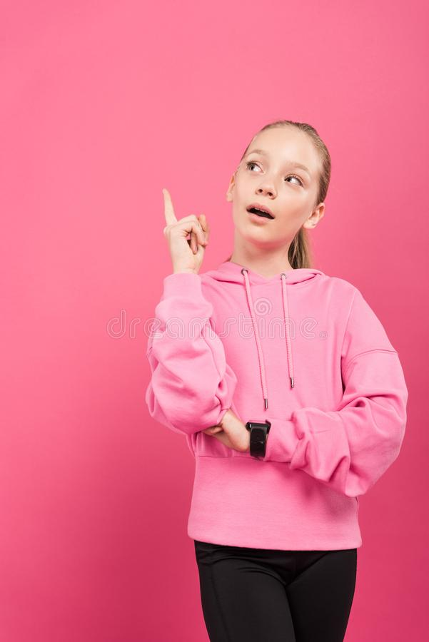 Adorable sportive kid pointing up and having idea, isolated. On pink stock photography