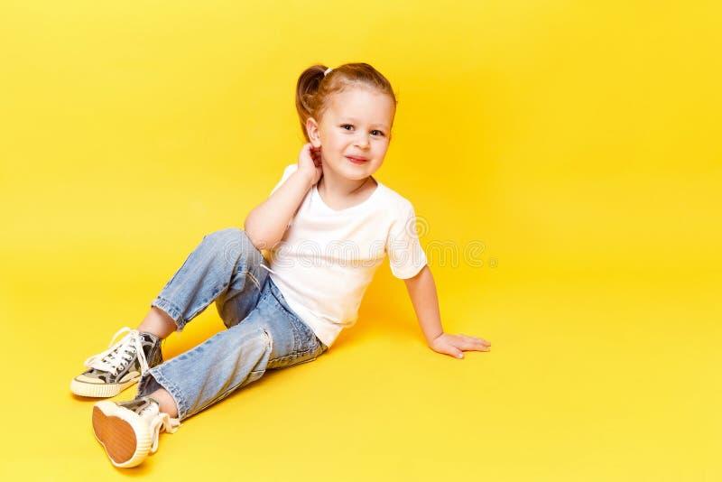 Adorable stylish girl posing on yellow background royalty free stock photos