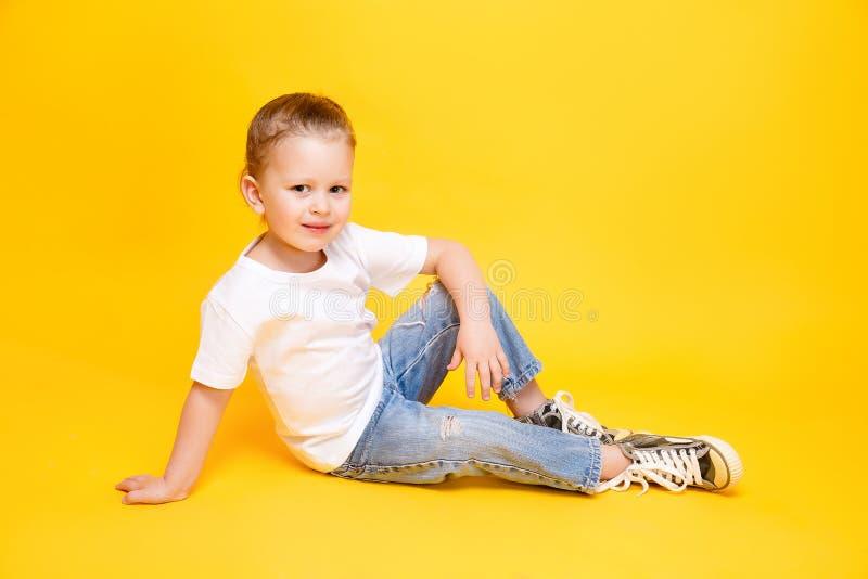 Adorable stylish girl posing on yellow background royalty free stock images