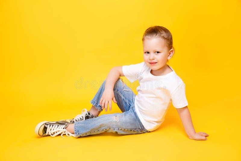 Adorable stylish girl posing on yellow background stock images