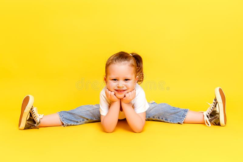 Adorable stylish girl posing on yellow background stock image