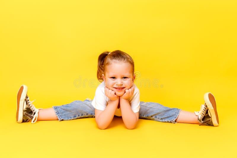 Adorable stylish girl posing on yellow background royalty free stock photo