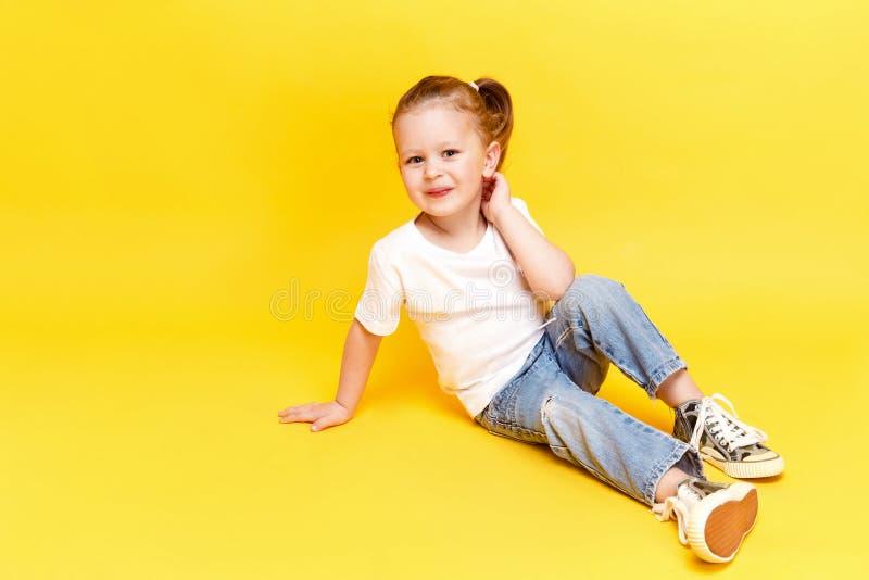 Adorable stylish girl posing on yellow background royalty free stock photography