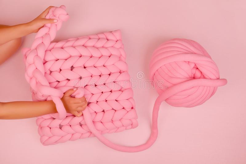 Adorable super chunky pink pillow. Girl knitting adorable super chunky pillow. Minimalistic pink background. Craft, handmade and skill stock photography