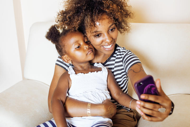 Adorable sweet young afro-american mother with cute little daughter, hanging at home, having fun playing smiling royalty free stock photo