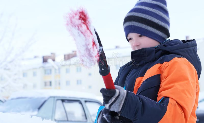 Adorable teen boy helping to brush a snow from a car. Adorable Caucasian teen boy helping to brush a snow from a car royalty free stock images