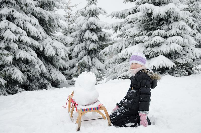 Adorable teen child having fun in happy winter time with lot of snow and little snowman stock image