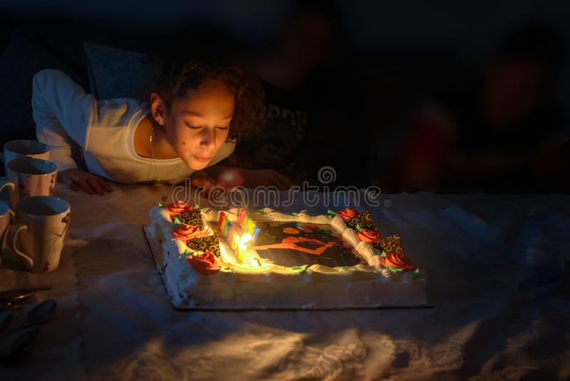 Adorable teen girl celebrating her birthday and blowing candles on beautiful Birthday chocolate cake. royalty free stock photo
