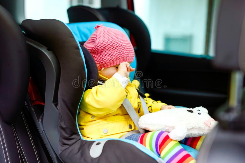 Adorable tired crying baby girl in colorful clothes sitting in car seat. Toddler child in winter clothes going on family royalty free stock images