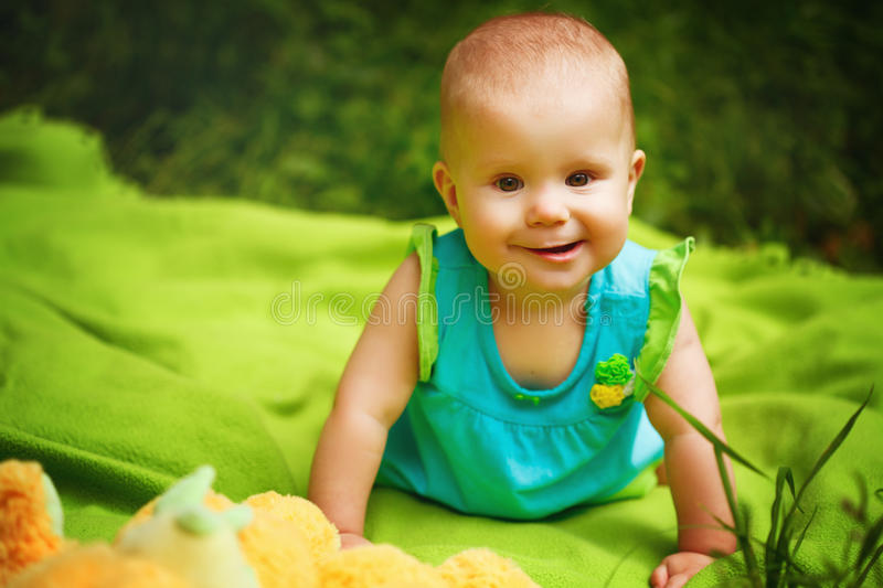 Adorable Toddler Baby Girl playing. Funny Toddler Baby Girl playing in the Park. Sitting on the blanket, smiling, looking to Camera stock images