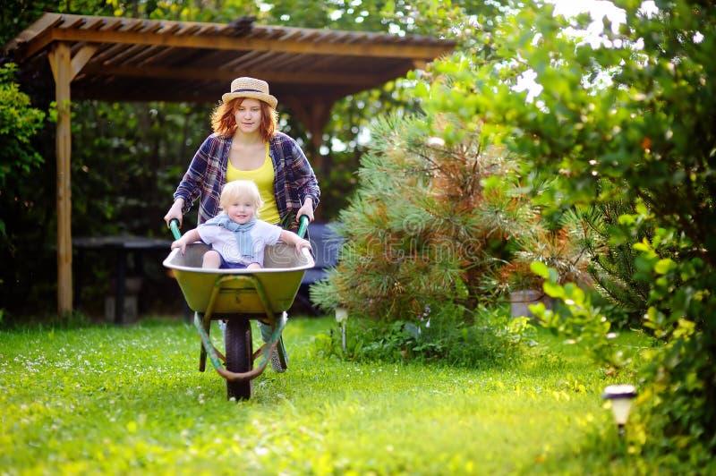 Adorable toddler boy having fun in a wheelbarrow pushing by mum in domestic garden, on warm sunny day stock image