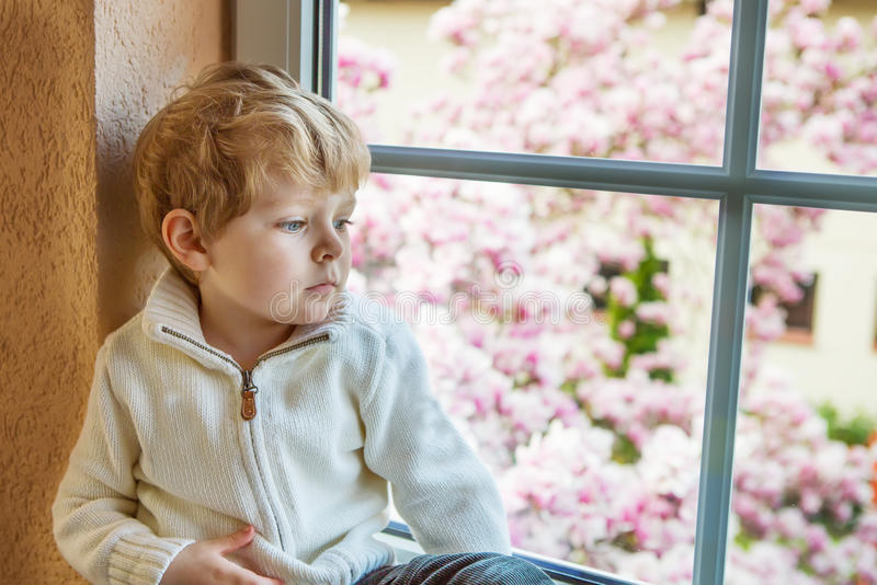 Adorable toddler boy looking out of the window stock image