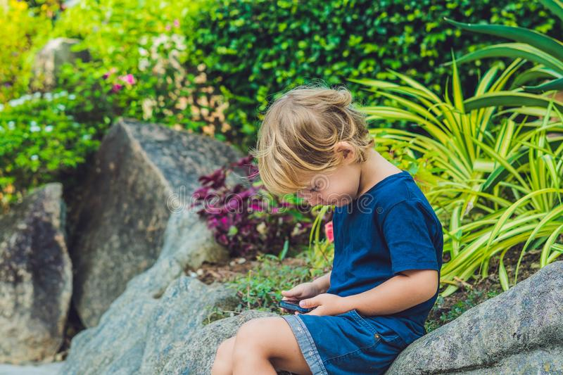 Adorable toddler boy sitting on the bench and playing with smartphone. Child learning how to use smartphone. Boy texting on the ph stock images