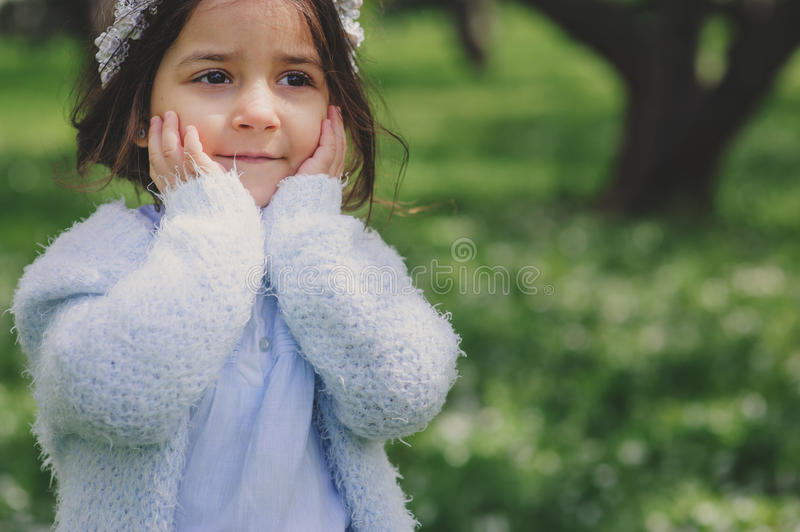Adorable toddler child girl in light blue dressy outfit walking and playing in blooming spring garden. Adorable toddler child girl in light blue dressy outfit royalty free stock images