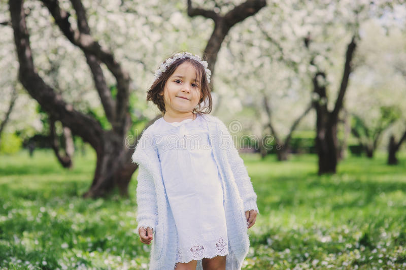 Adorable toddler child girl in light blue dressy outfit walking and playing in blooming spring garden. Adorable toddler child girl in light blue dressy outfit stock photo