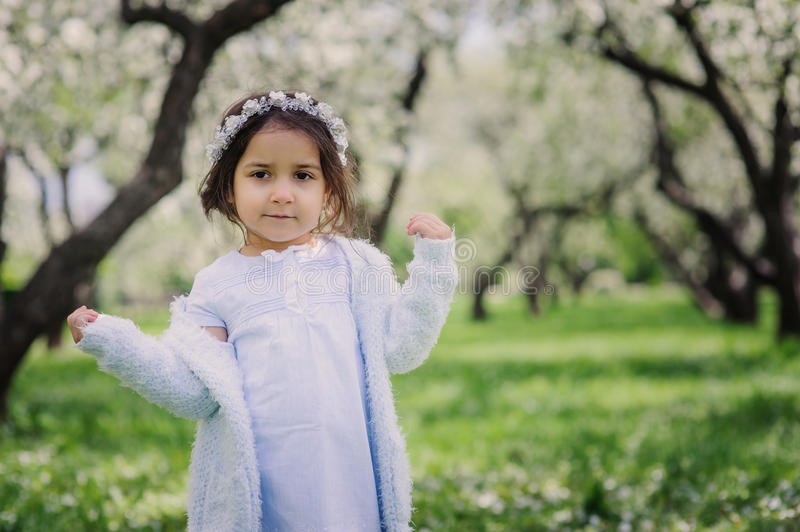 Adorable toddler child girl in light blue dressy outfit walking and playing in blooming spring garden. Adorable toddler child girl in light blue dressy outfit stock image