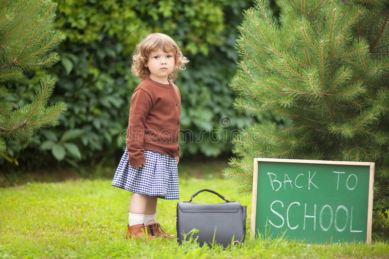 Adorable toddler girl; back to school written on chalk blackboard. Caucasian toddler child kid girl looking with serious face, back to school. Fall outdoors royalty free stock images