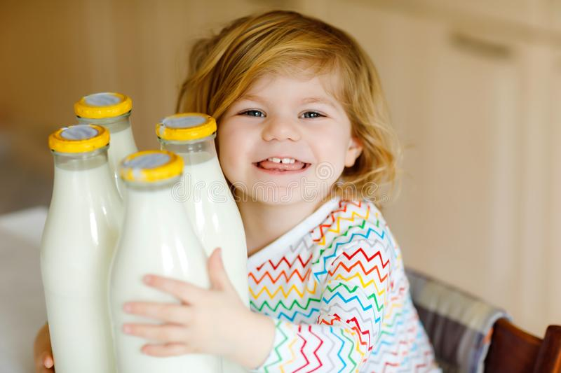 Adorable toddler girl drinking cow milk for breakfast. Cute baby daughter with lots of bottles. Healthy child having royalty free stock photography